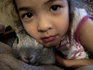 Une enfant et son lapin gris