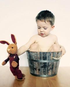 peluche doudou lapin et un bébé dans un bac en bois